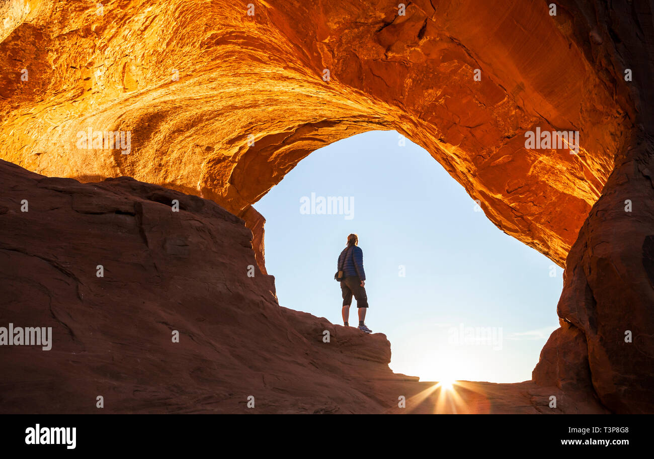 A woman standing in the arch at Looking Glass Rock as the sun rises, Utah, USA. - Stock Image