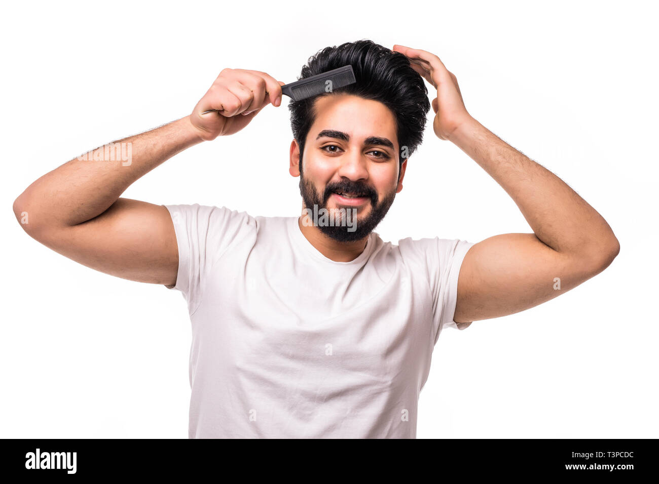 Barber shop concept. Smiling handsome young brunet in white t shirt is standing on the pure background, brushing his hair. His hairdo is stylish and t Stock Photo