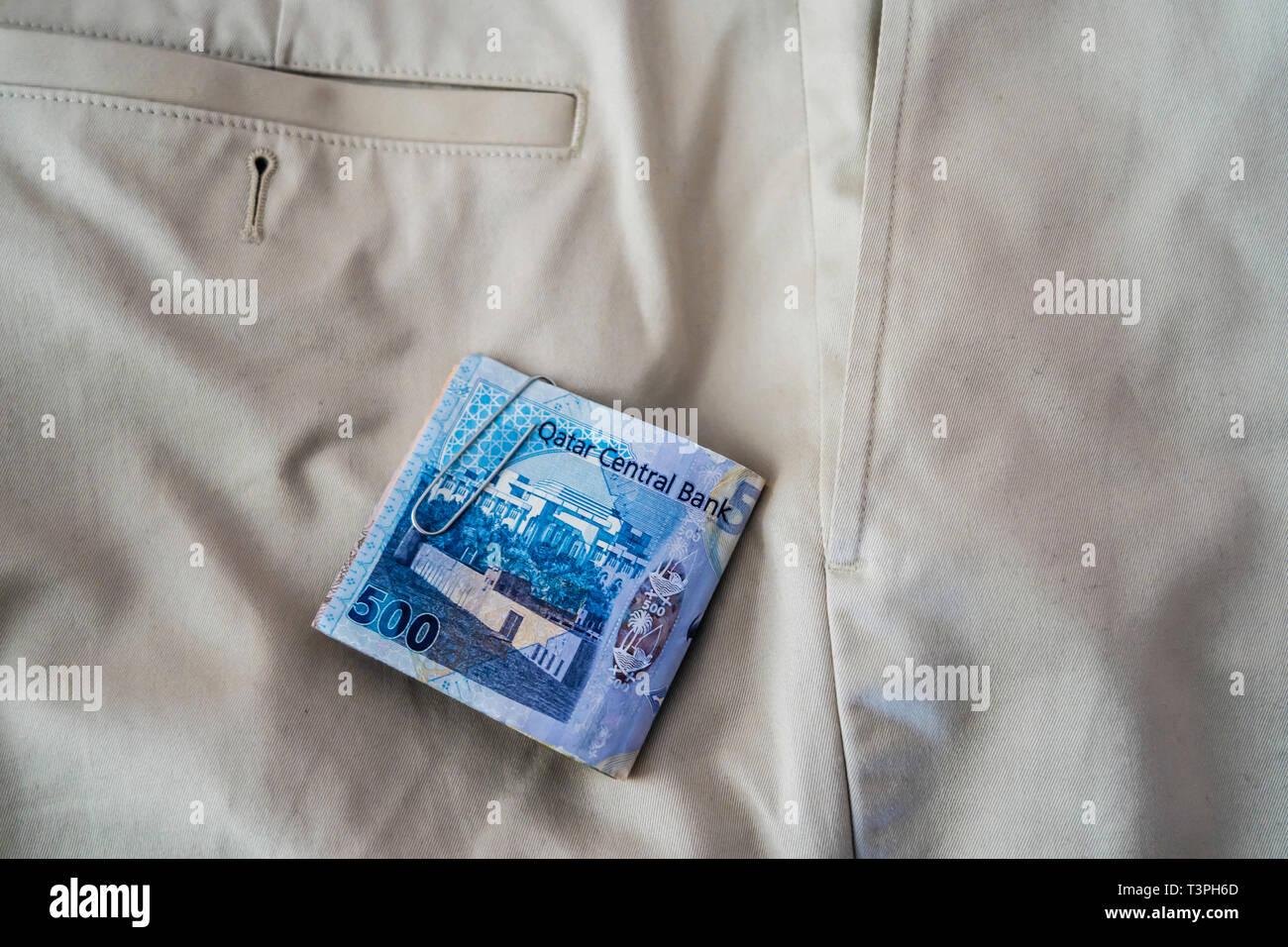 Qatari Riyal notes falling out of trouser or Pants Pockets Stock Photo
