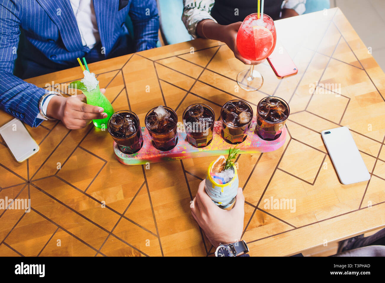 Group of friends drinking cocktails fashion bar restaurants - Side view point of people hands with smartphone - Social gathering concept with addicted - Stock Image