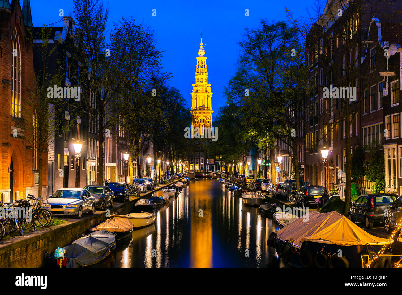 Amsterdam Zuiderkerk church tower at the end of a canal in the city of Amsterdam, Netherlands at night . - Stock Image
