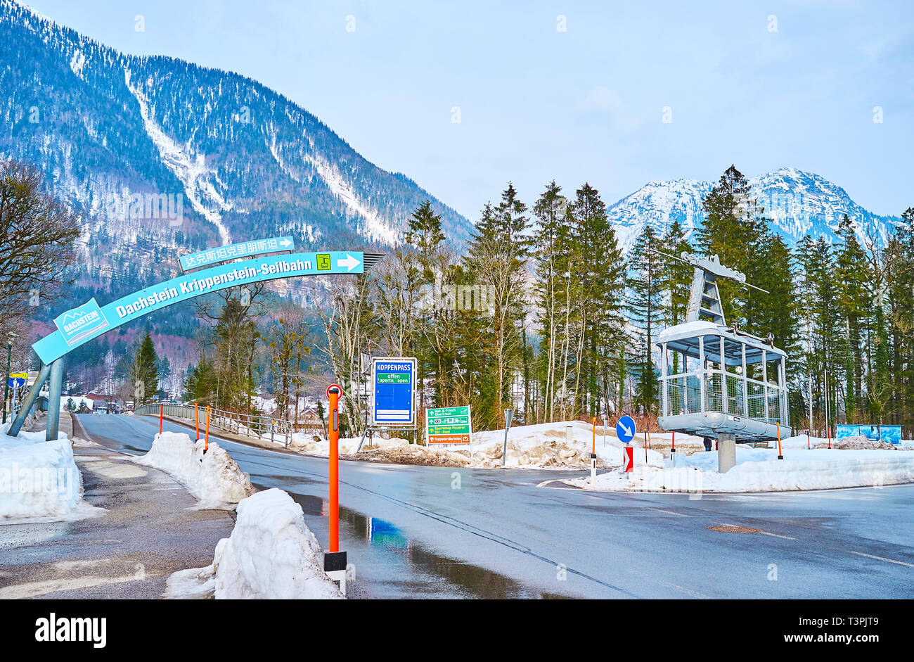 OBERTRAUN, AUSTRIA - FEBRUARY 21, 2019: The road intersection with signpost to Dachstein-Krippenstein cable car and vintage air lift gondola, as the m - Stock Image