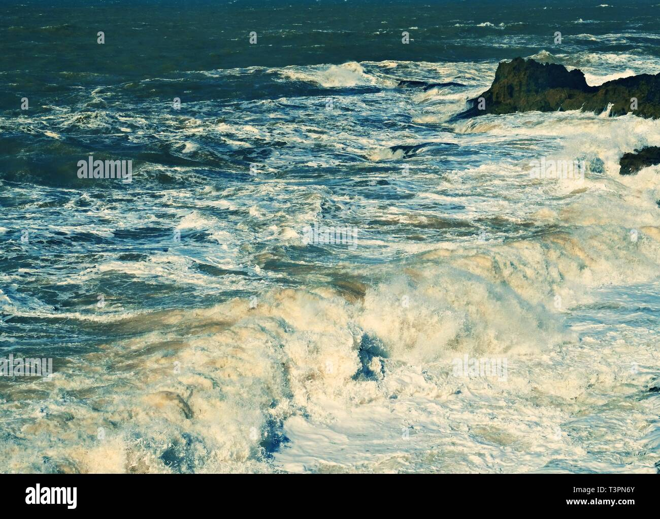 Stormy waves with splashes and foam on the ocean surface during a storm - Stock Image