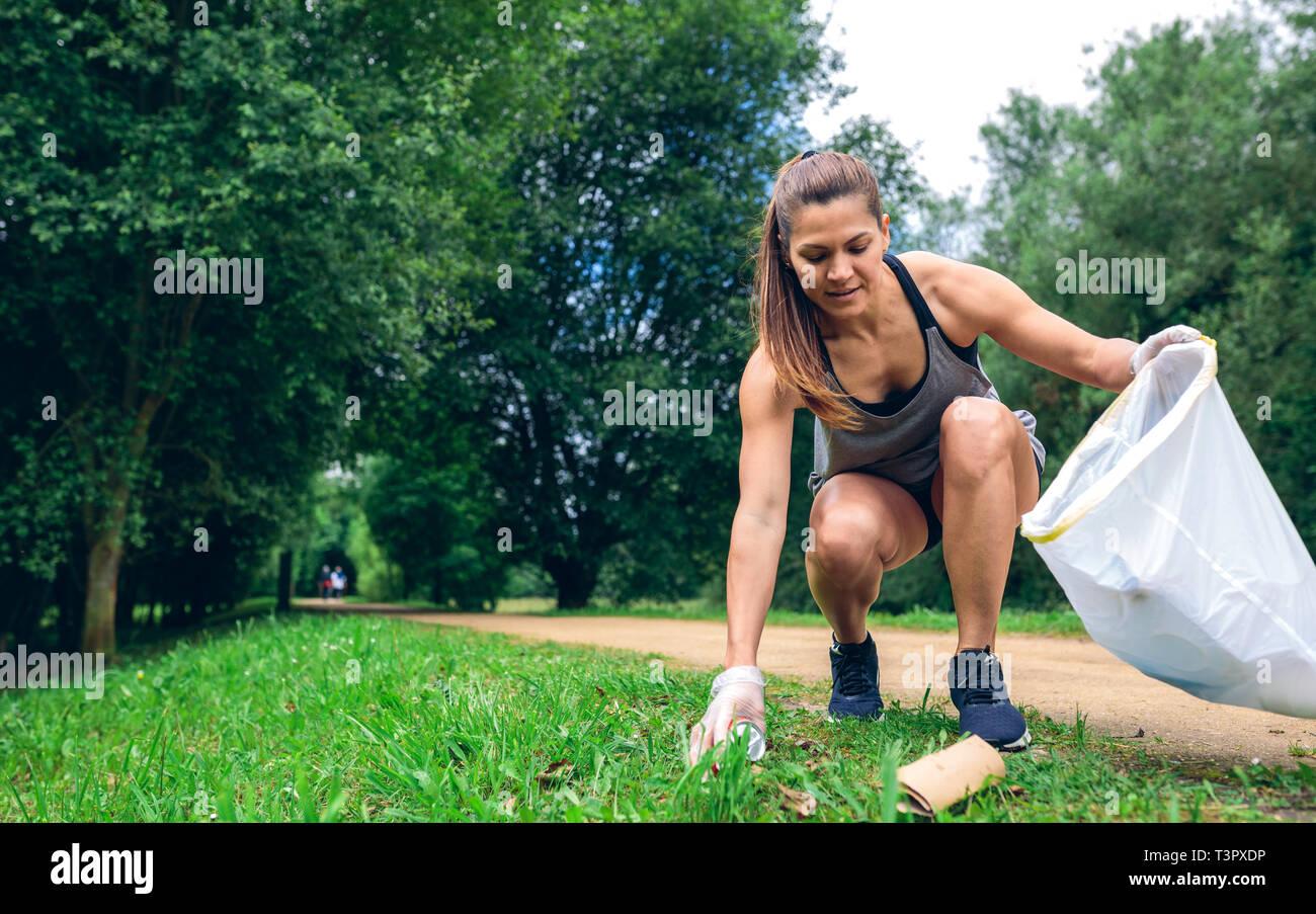 Girl with garbage bag doing plogging Stock Photo