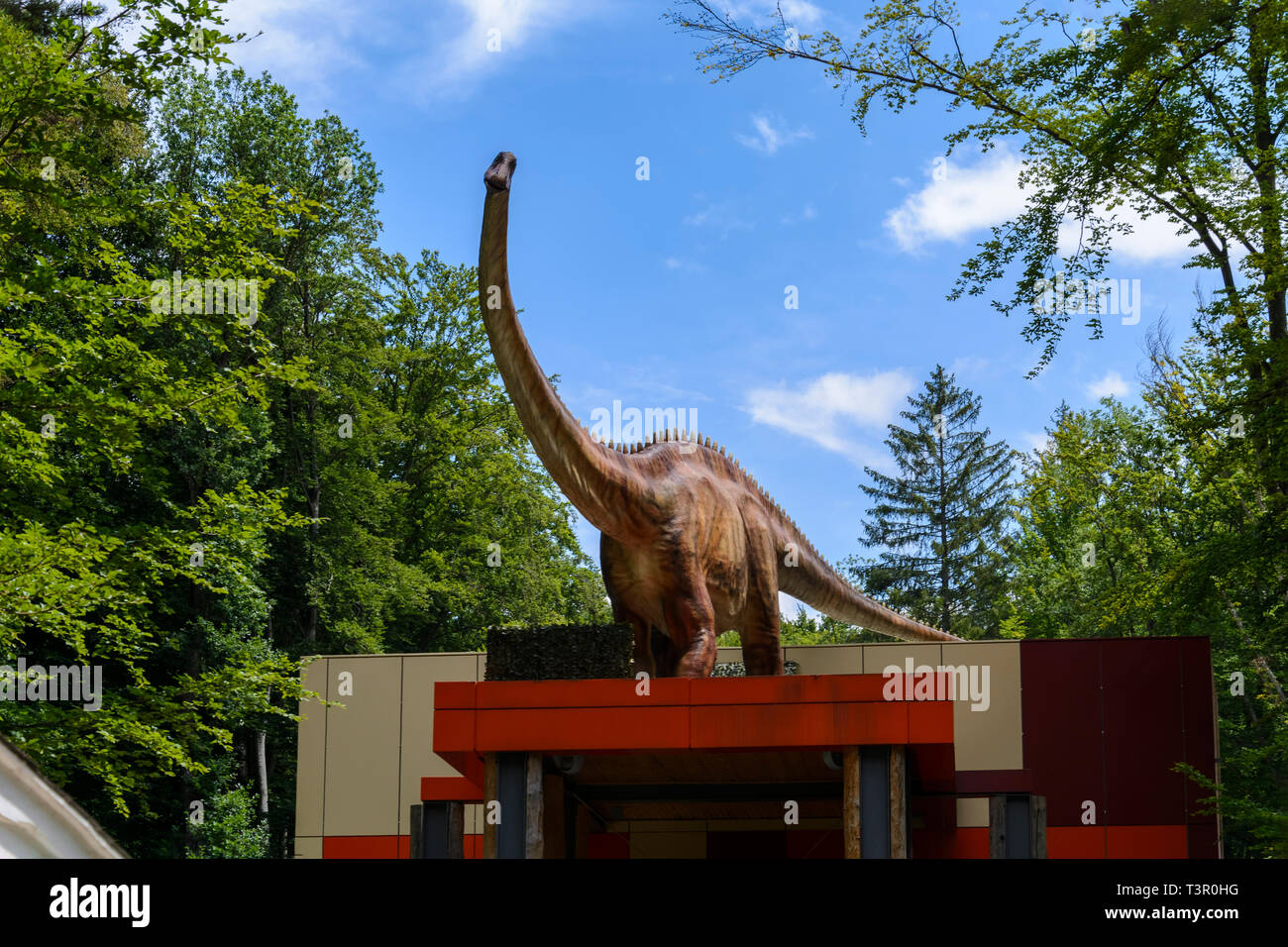 big dinosaur in a forest, guarding a entrance Stock Photo