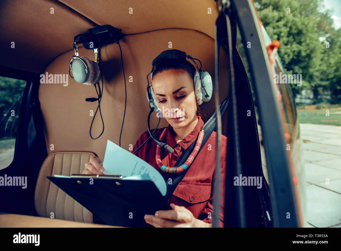 Concentrated dark-haired businesswoman flipping through documents while wearing headphones - Stock Image