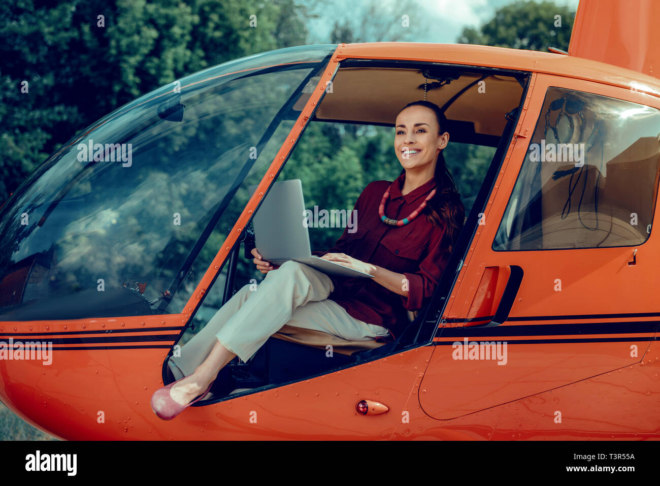 Resolute cheerful lady in light pants and red shirt resting in helicopter - Stock Image