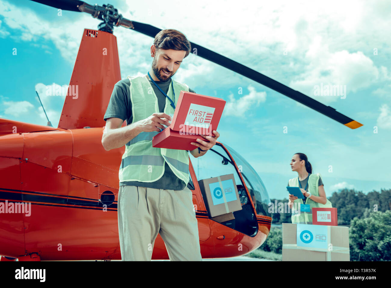 Attentive experienced bearded volunteer checking inside of first aid box - Stock Image