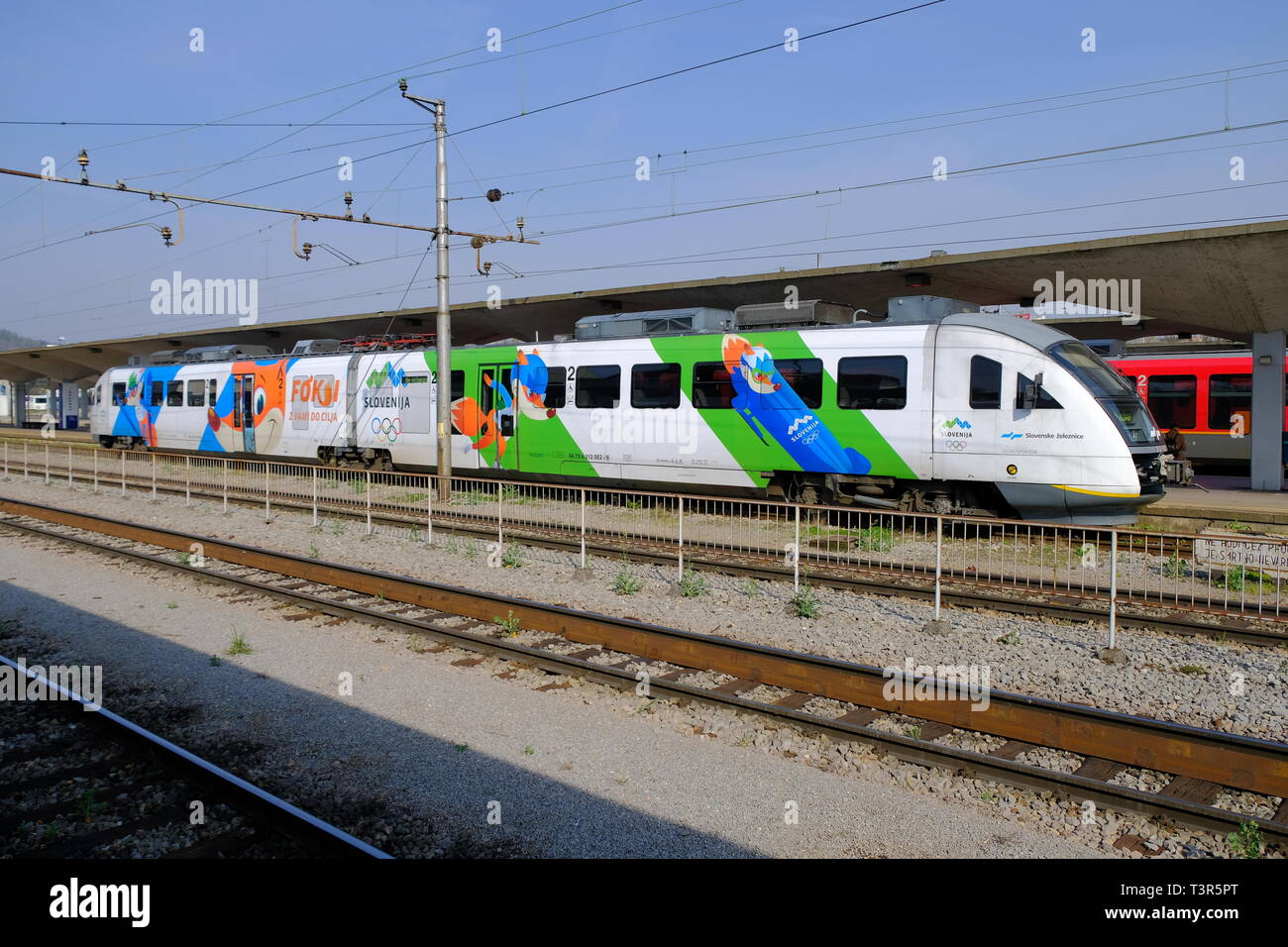 Slovenian train featuring design of the national Olympic winter team sitting in Ljubljana train station. with Foksi the Mascot in various disciplines Stock Photo