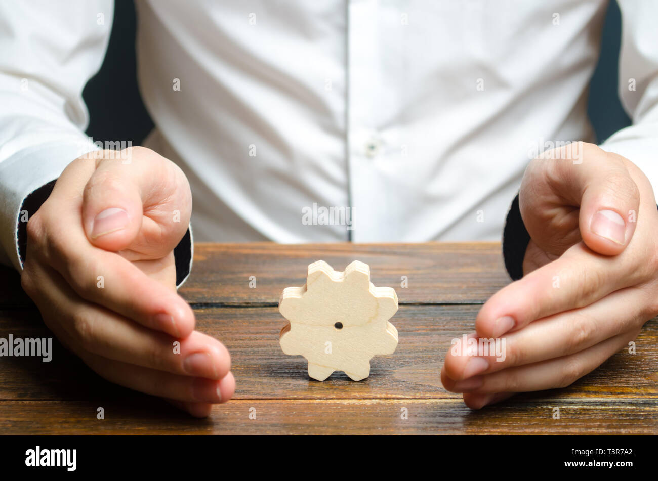 Businessman and wooden gear. Establishing business processes and communications. Development of business relations and cooperation. Efficiency increas - Stock Image
