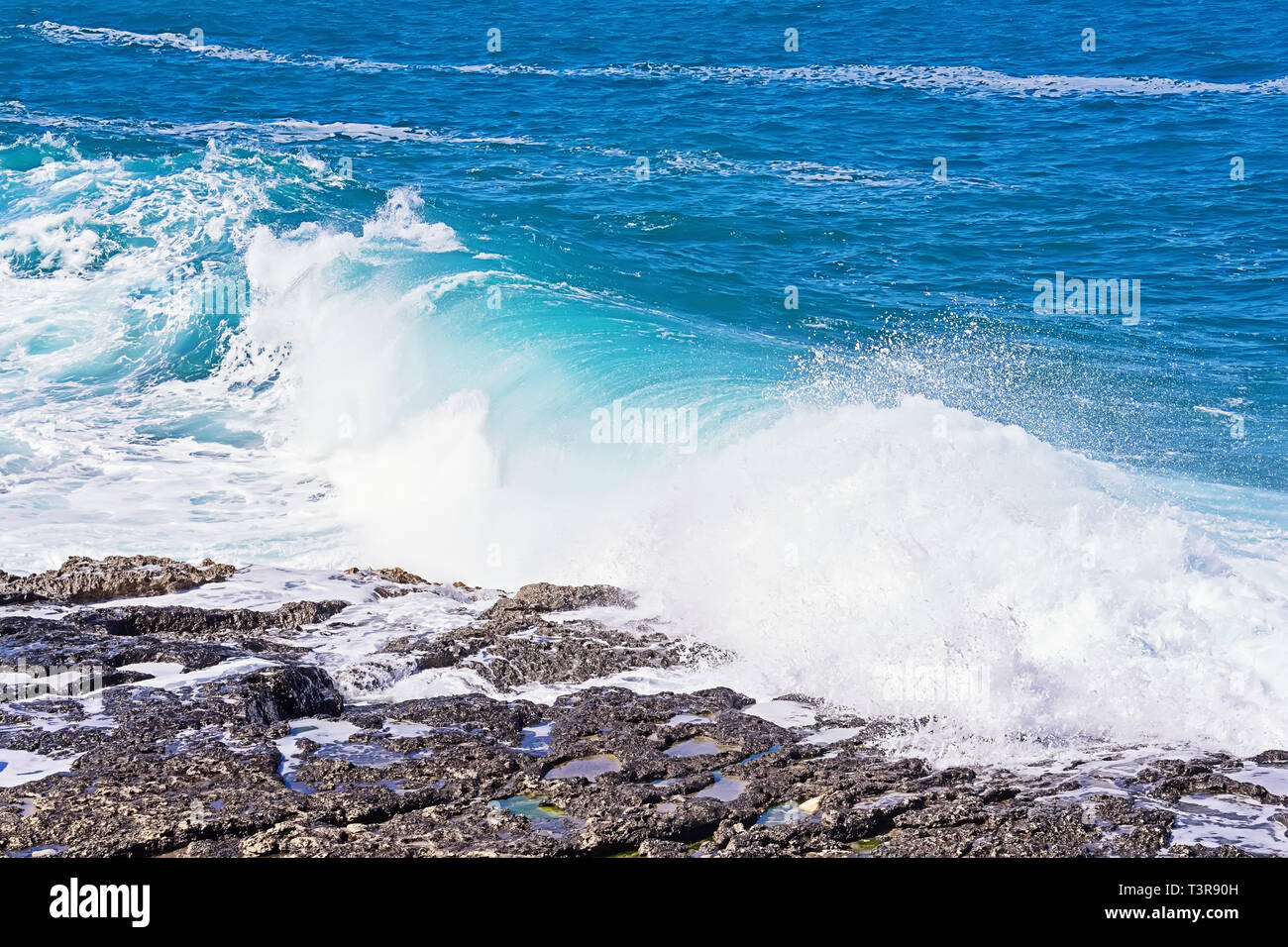 Beautiful blue wave rolls on stony beach with splash and foam. Summer background and texture, copy space - Stock Image