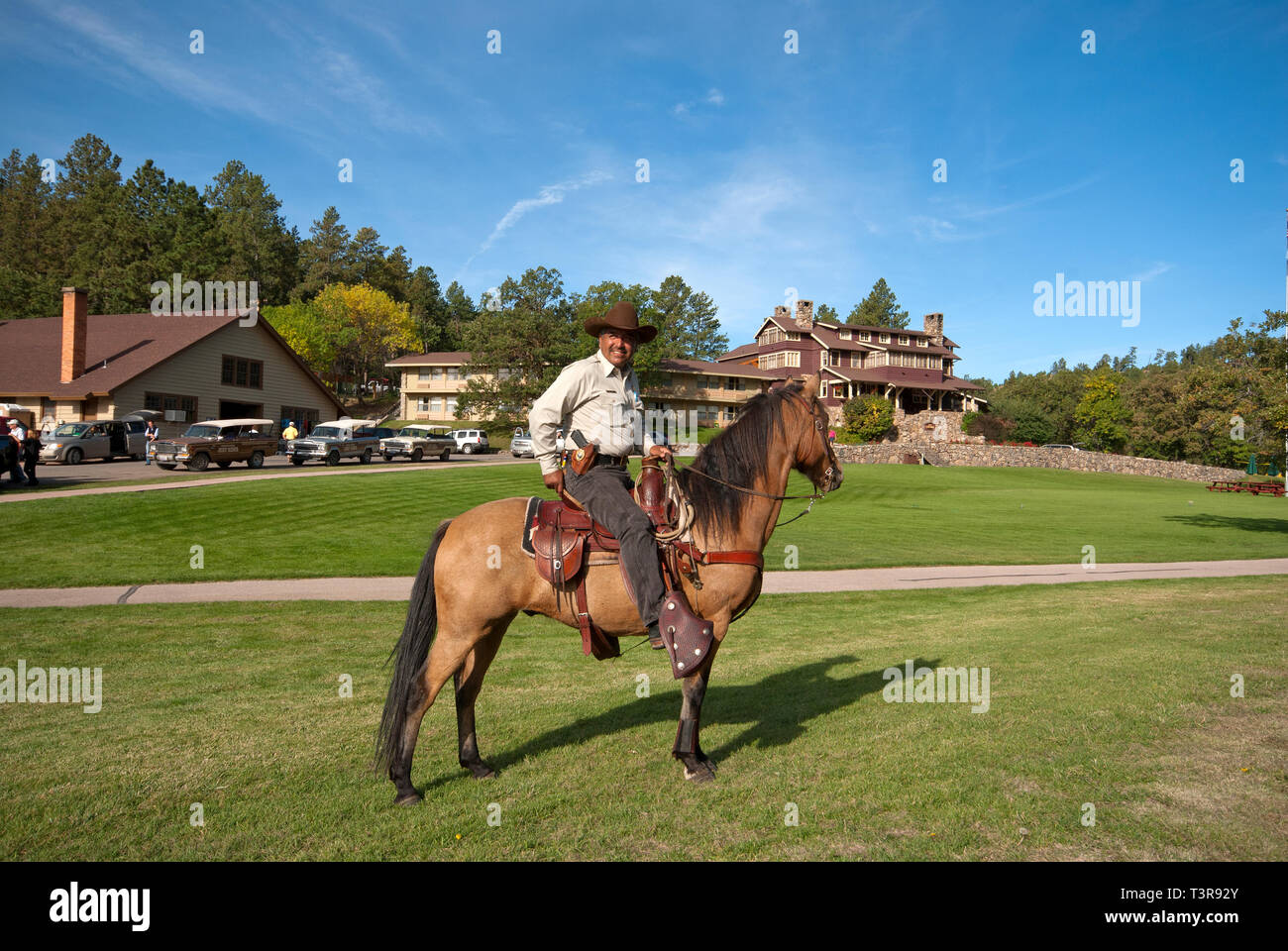 Park ranger on his horse near the State Game Lodge (in the background), Custer State Park, Black Hills, South Dakota, USA - Stock Image