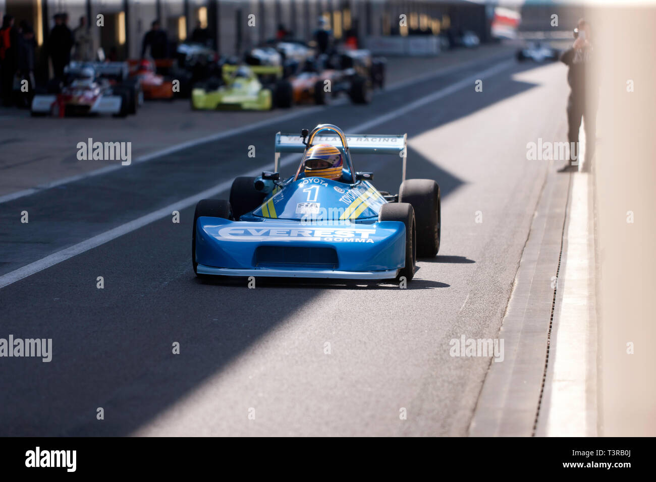View of Kieth White driving his 1977, Ralt RT1 Formula 3 race car down the Pit Lane, at the 2019 Silverstone Classic media day/ Test Day - Stock Image