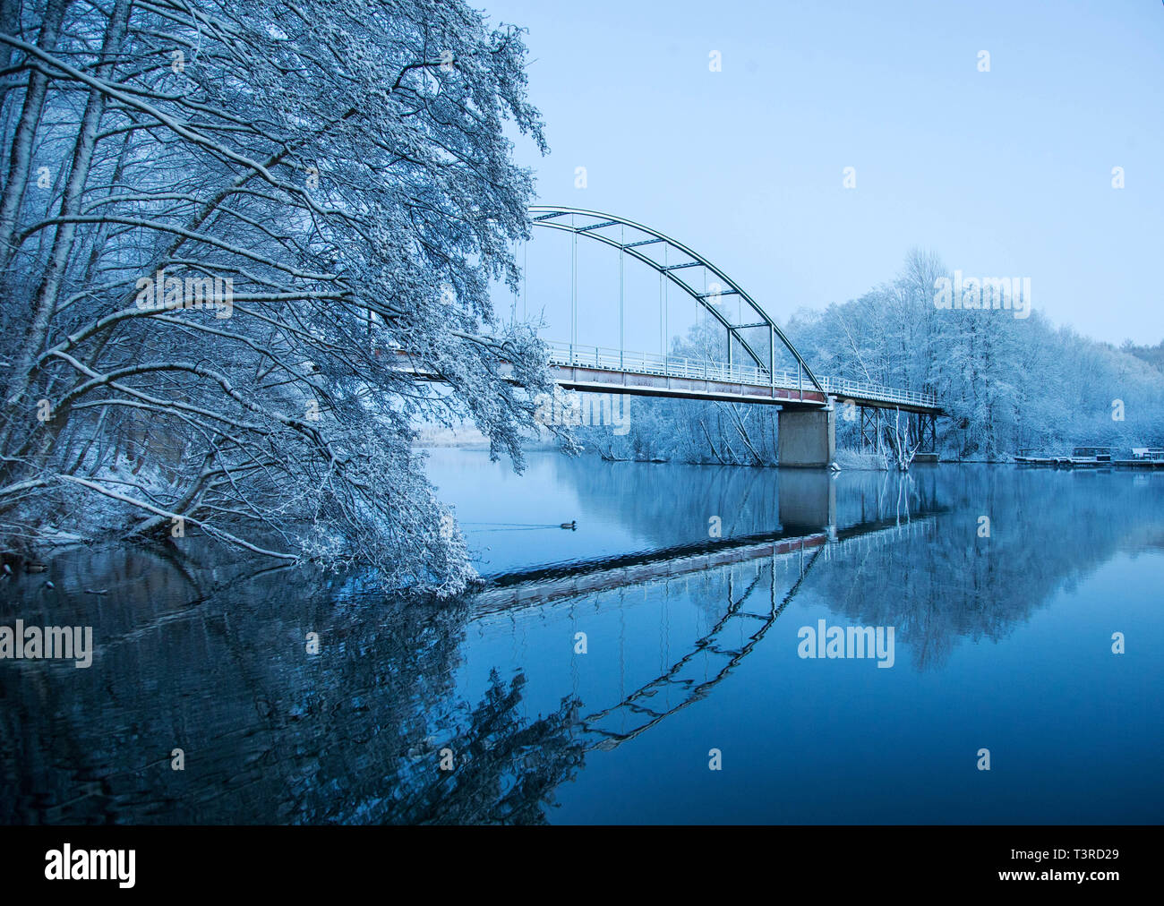 Chilly weather with snow and frost on the trees a cold winter day by a bridge over water. - Stock Image