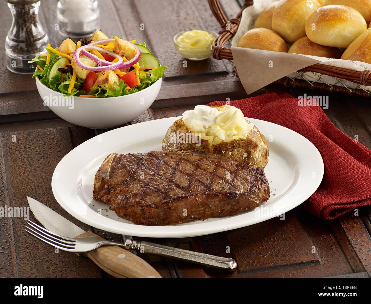 Kansas City Steak with baked potato and salad - Stock Image