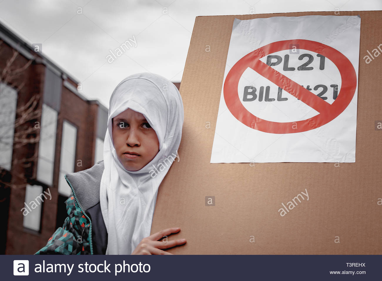 April 7, 2019 - Montreal, Canada: A veiled little girl, looking angry, holds a sign opposing Bill 21, during the demonstration against Bill 21 on secu - Stock Image