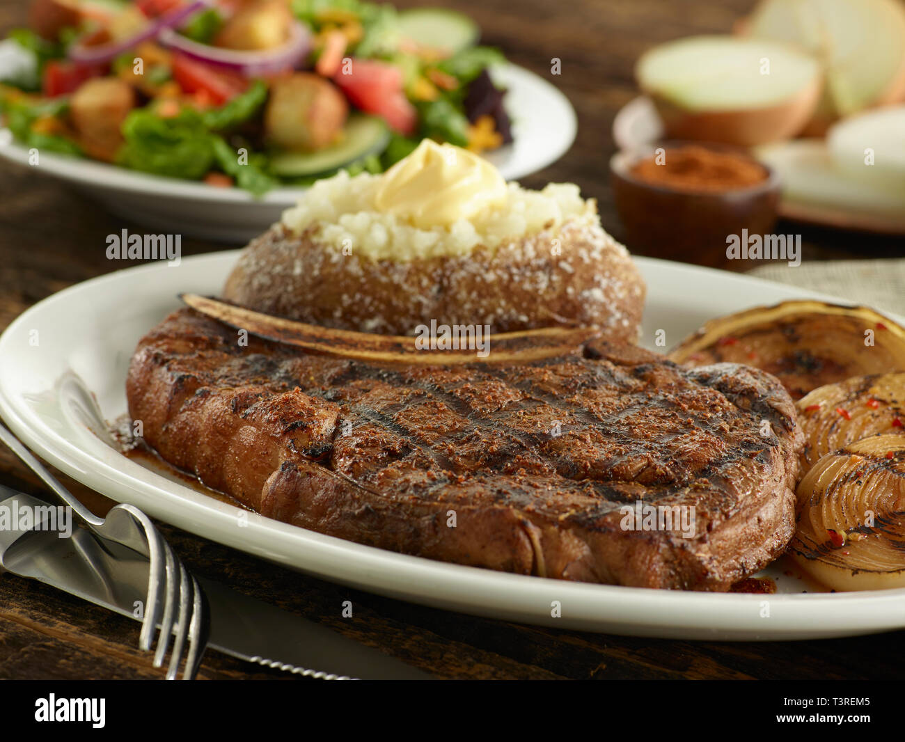 Blackened Ribeye Steak with grilled onions and salad - Stock Image