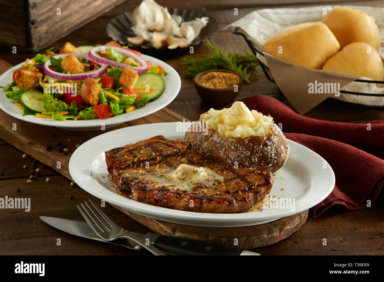 Kanas City Bone in Strip Steak with baked potato, salad, and dinner rolls - Stock Image