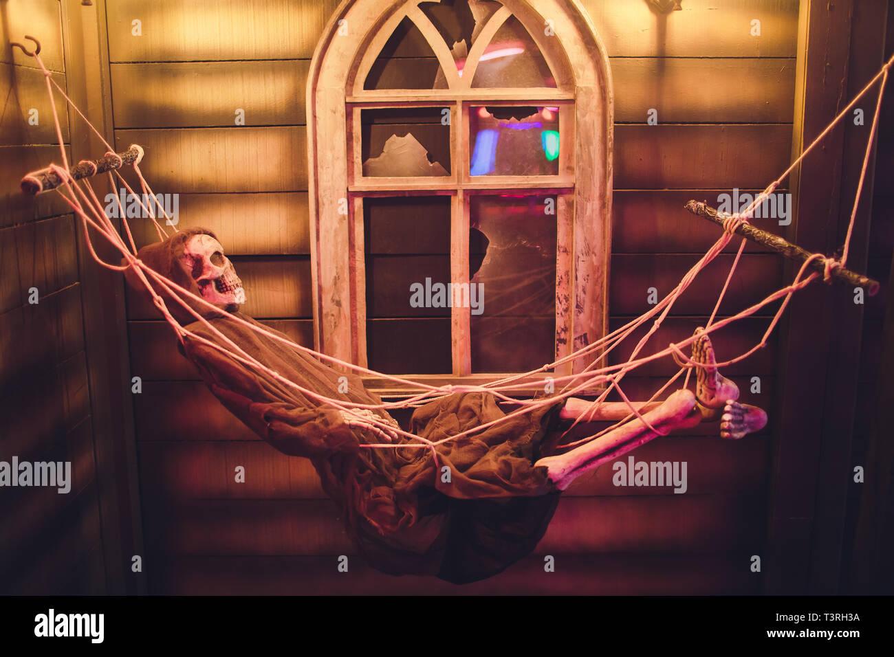 Human skeleton swinging on hammock against the window of the house. - Stock Image