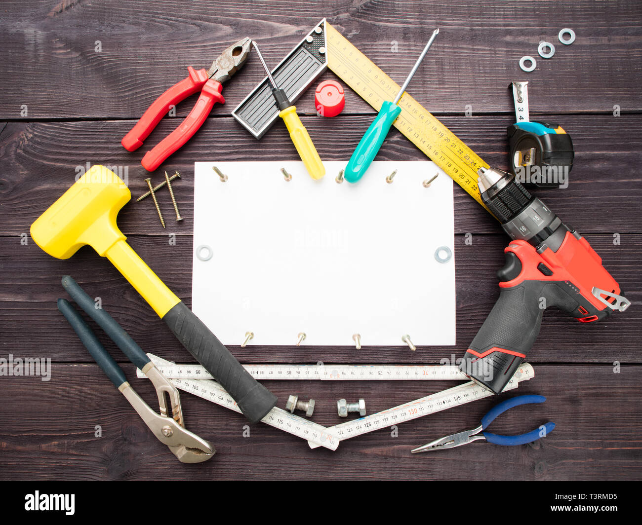 The tool building on the wooden background around the white sheet of paper Stock Photo