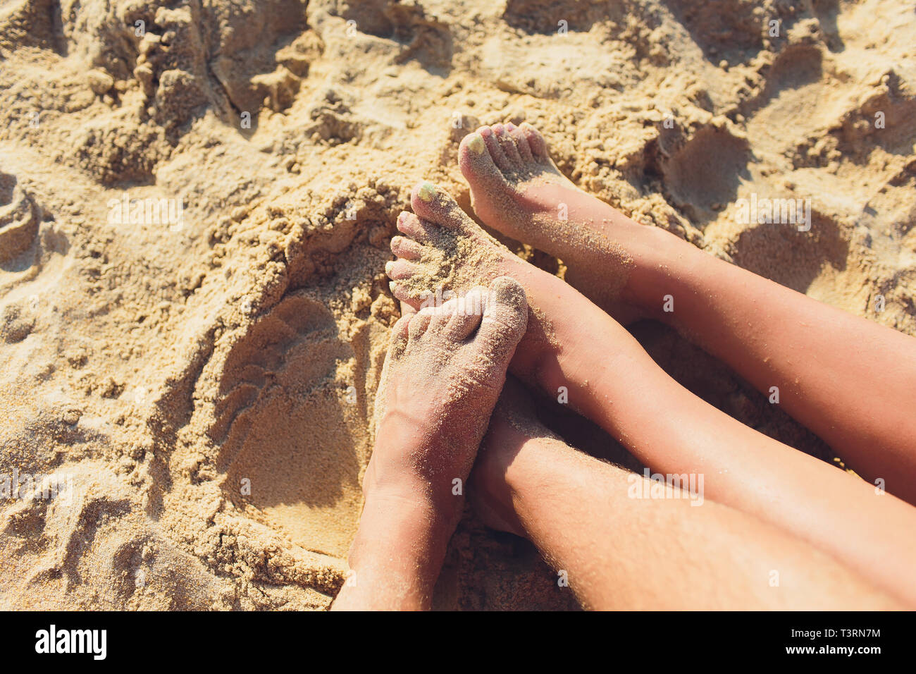 Woman tanned legs on sand beach. Travel concept. Happy feet in tropical paradise. - Stock Image