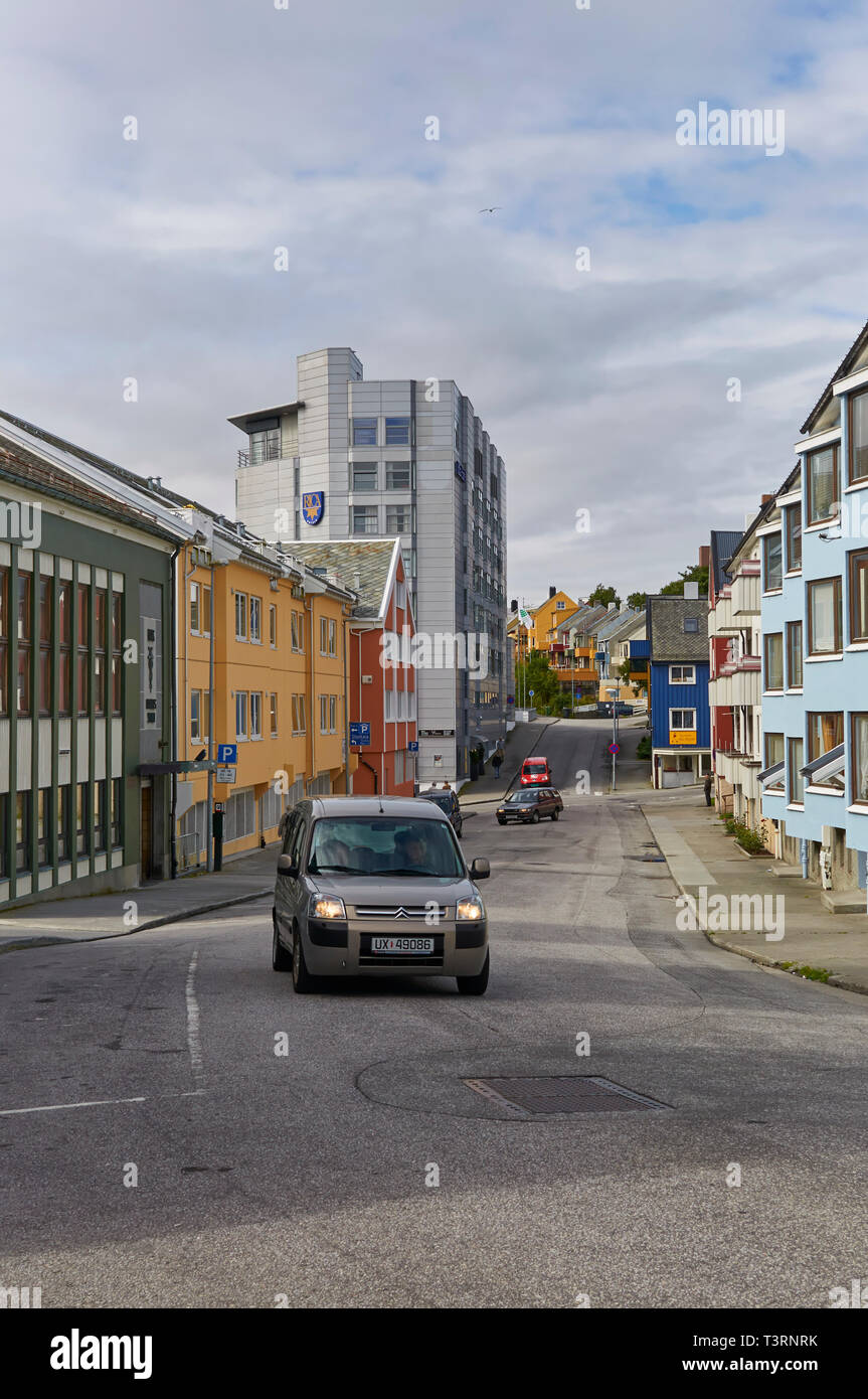 Looking down a street in Kristiansund Norway with Cars driving past on the road and empty pavements early morning in Summer. - Stock Image