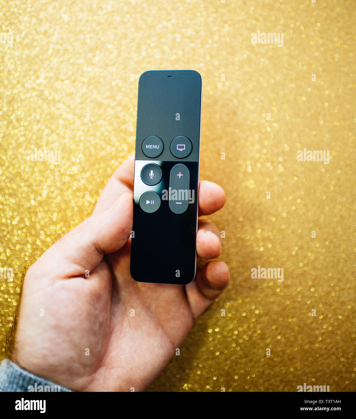 Paris, France - 25 Mar 2019: Man hand holding against modern sparkle holiday yellow background remote control of Apple TV 4k player with Siri assistant - Stock Image