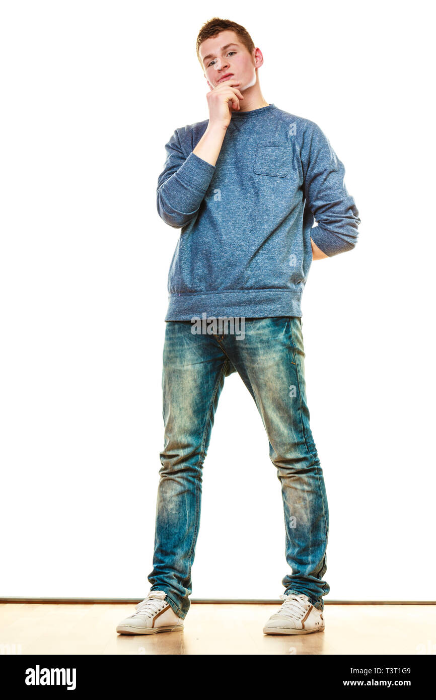 Young fashionable man teen boy in full length casual style blue jeans thoughtful expression isolated on white - Stock Image