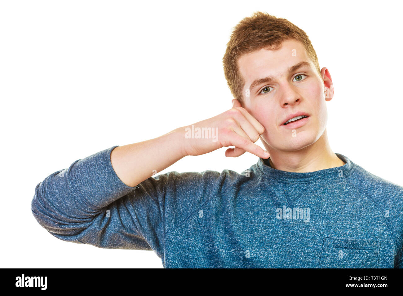 Communication concept. Young man making call me gesture. Blonde teen boy with phone hand sign isolated on white - Stock Image