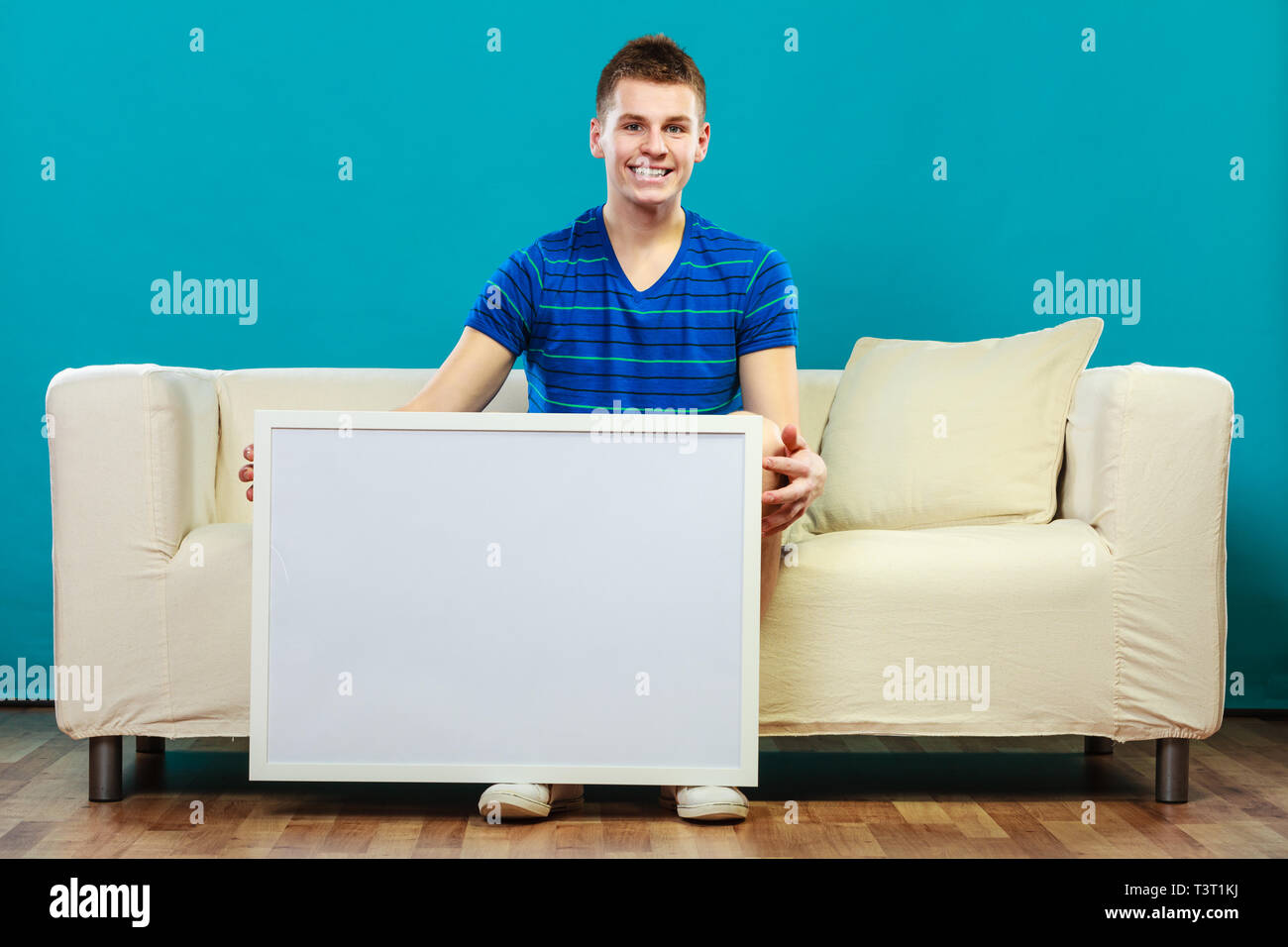 Advertisement concept. Young man sitting on sofa with blank presentation board. Male model showing banner sign billboard copy space for text on blue - Stock Image