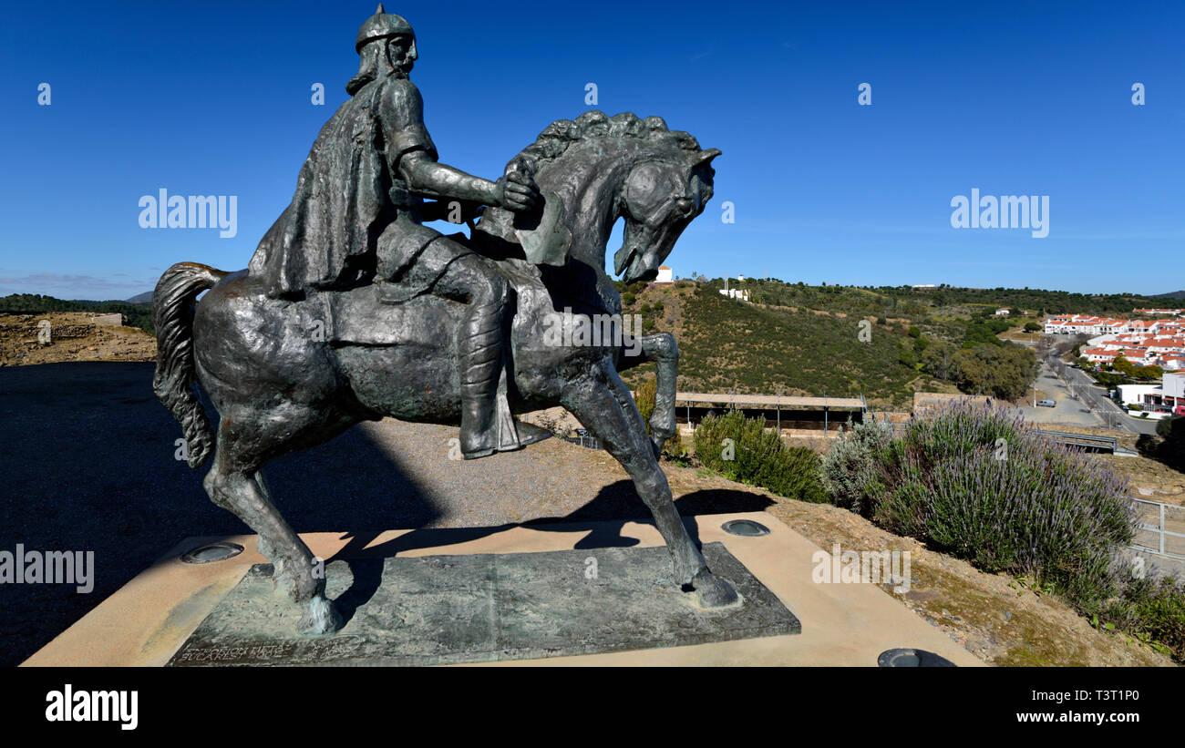 Equestrian bronze statue of moorish soldier overlooking village - Stock Image