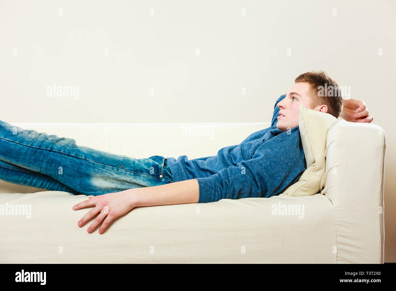 Home, leisure concept. Young handsome pensive man relaxing on couch laying and dreaming - Stock Image
