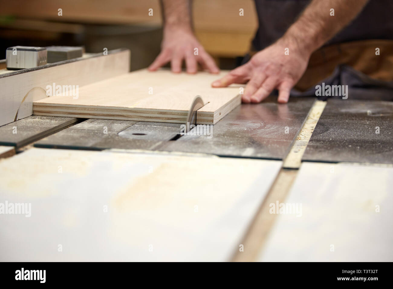 Carpenter using table saw in workshop Stock Photo