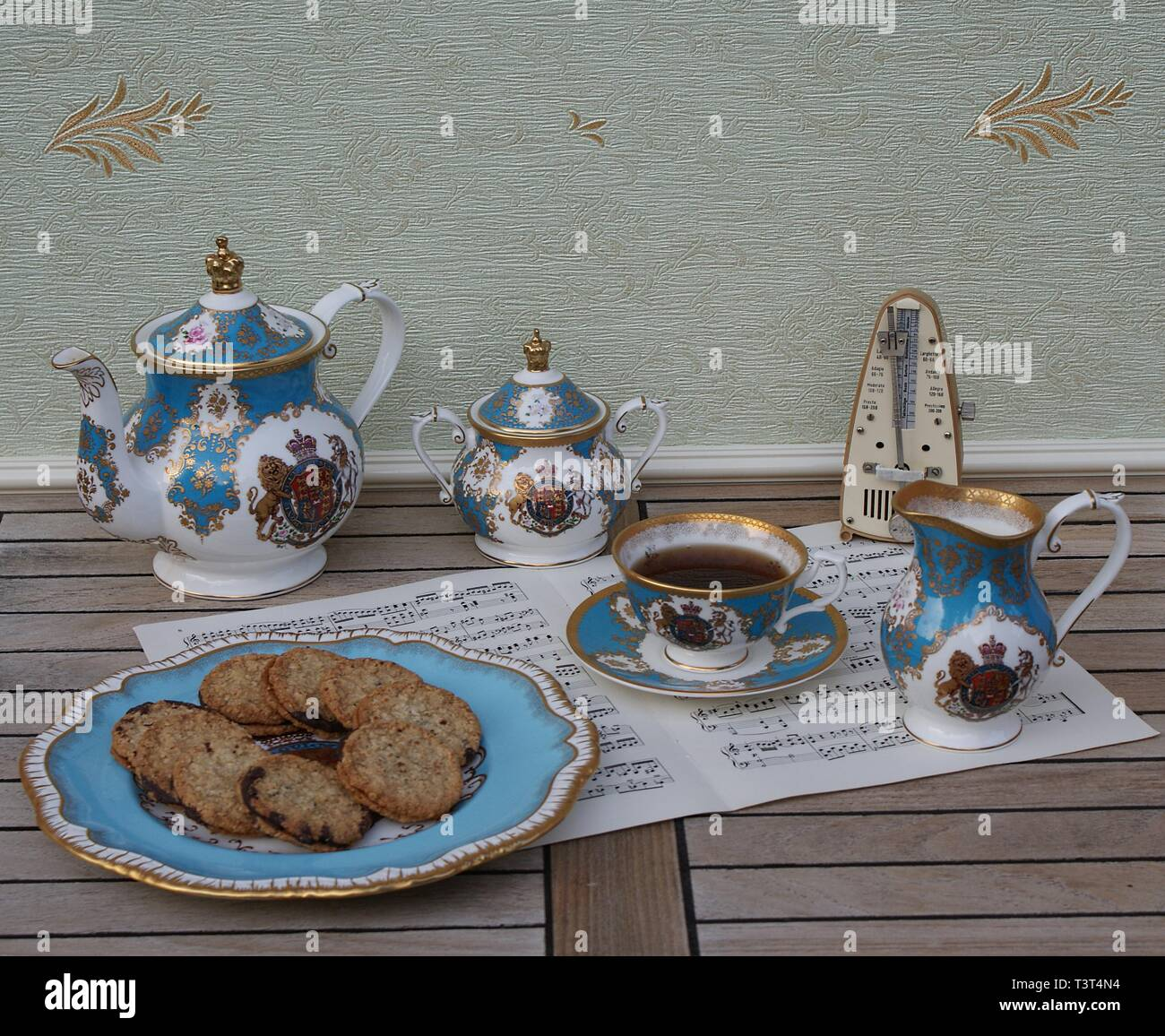 English teacup with saucer, teapot, sugar bowl, cream jug and a cake plate with cookies and a metronome for music on a sheet of music - Stock Image