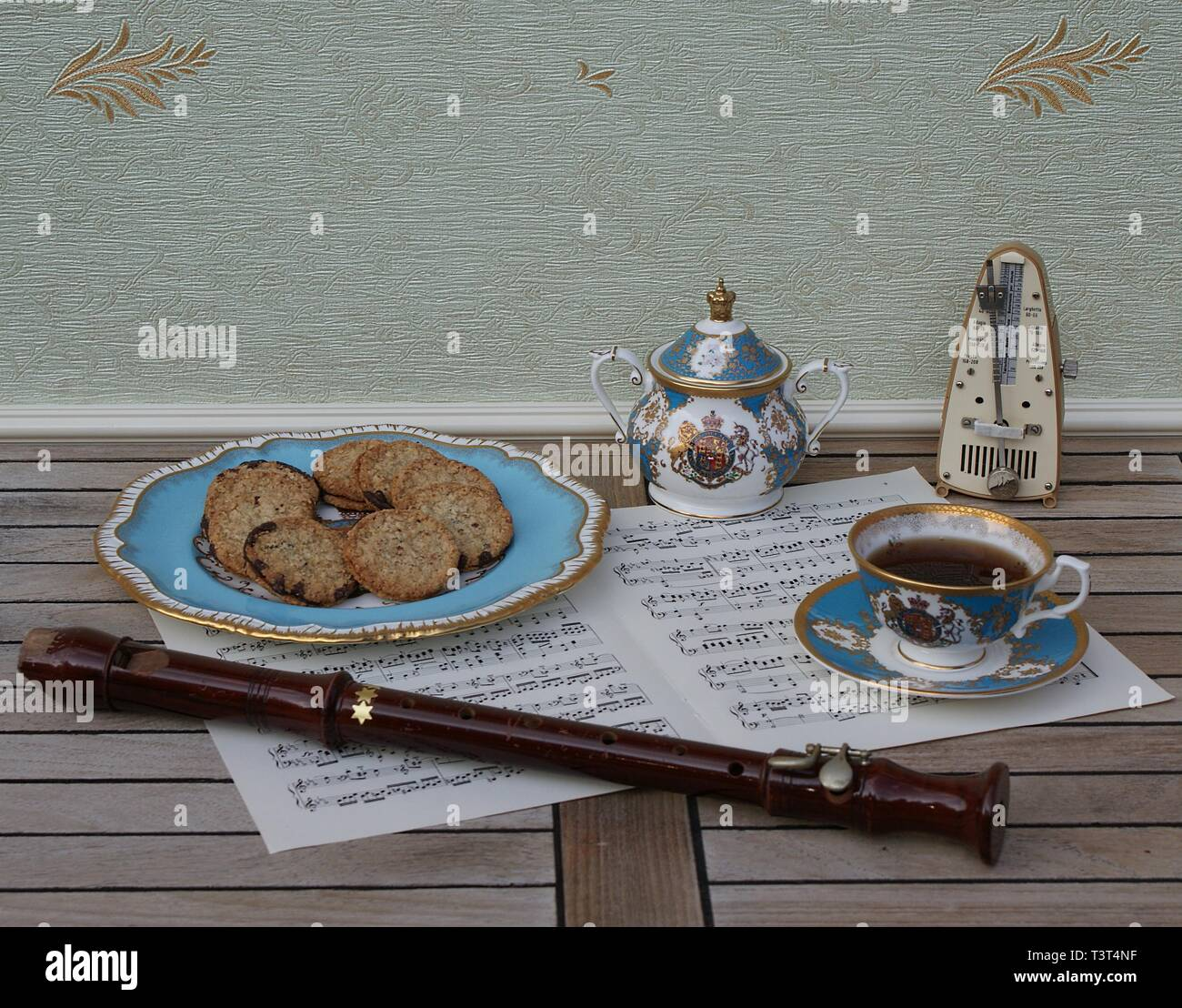 English teacup with saucer, sugar bowl and a cake plate with cookies, fine bone china porcelain, metronome for music a block flute on a sheet of music - Stock Image