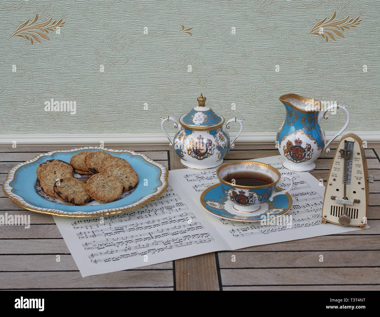 English teacup with saucer, sugar bowl, cream jug and a cake plate with cookies, fine bone china porcelain, a metronome for music on a sheet of music - Stock Image