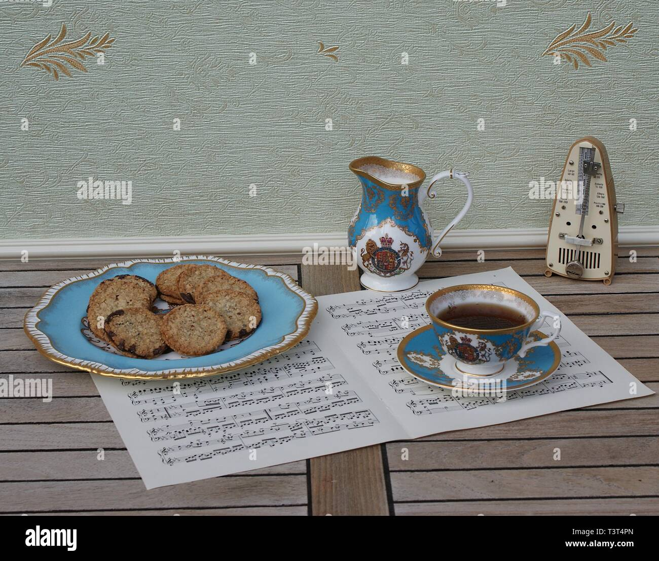 English teacup with saucer, cream jug and a cake plate with cookies, fine bone china porcelain, and a metronome for music on a sheet of music - Stock Image