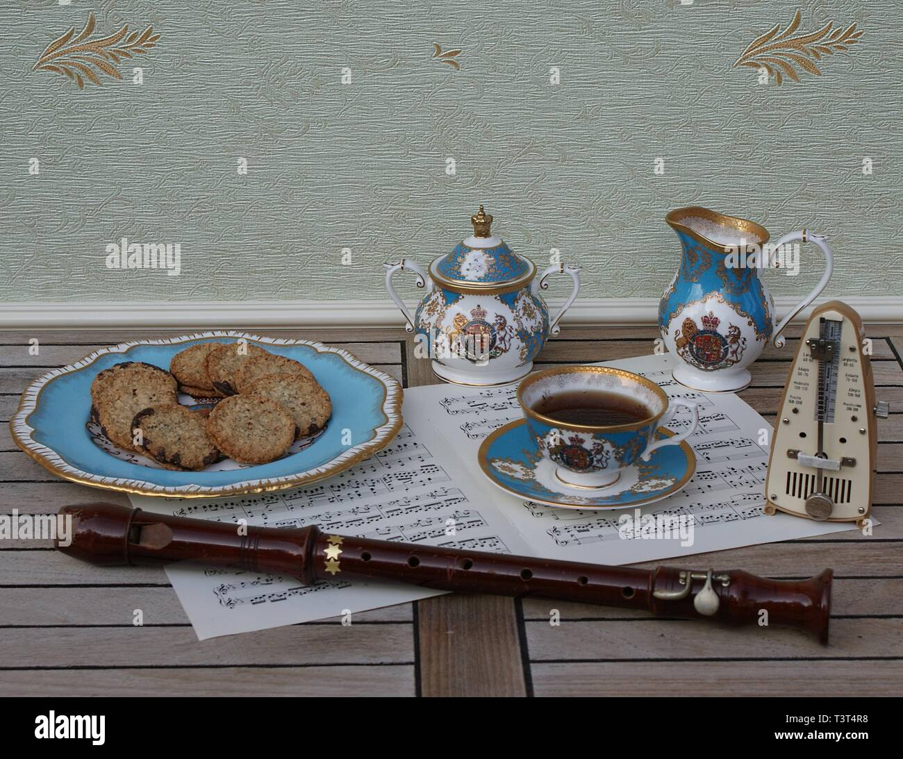 English teacup with saucer, sugar bowl, cream jug and a cake plate with cookies, metronome for music and a block flute on a sheet of music - Stock Image