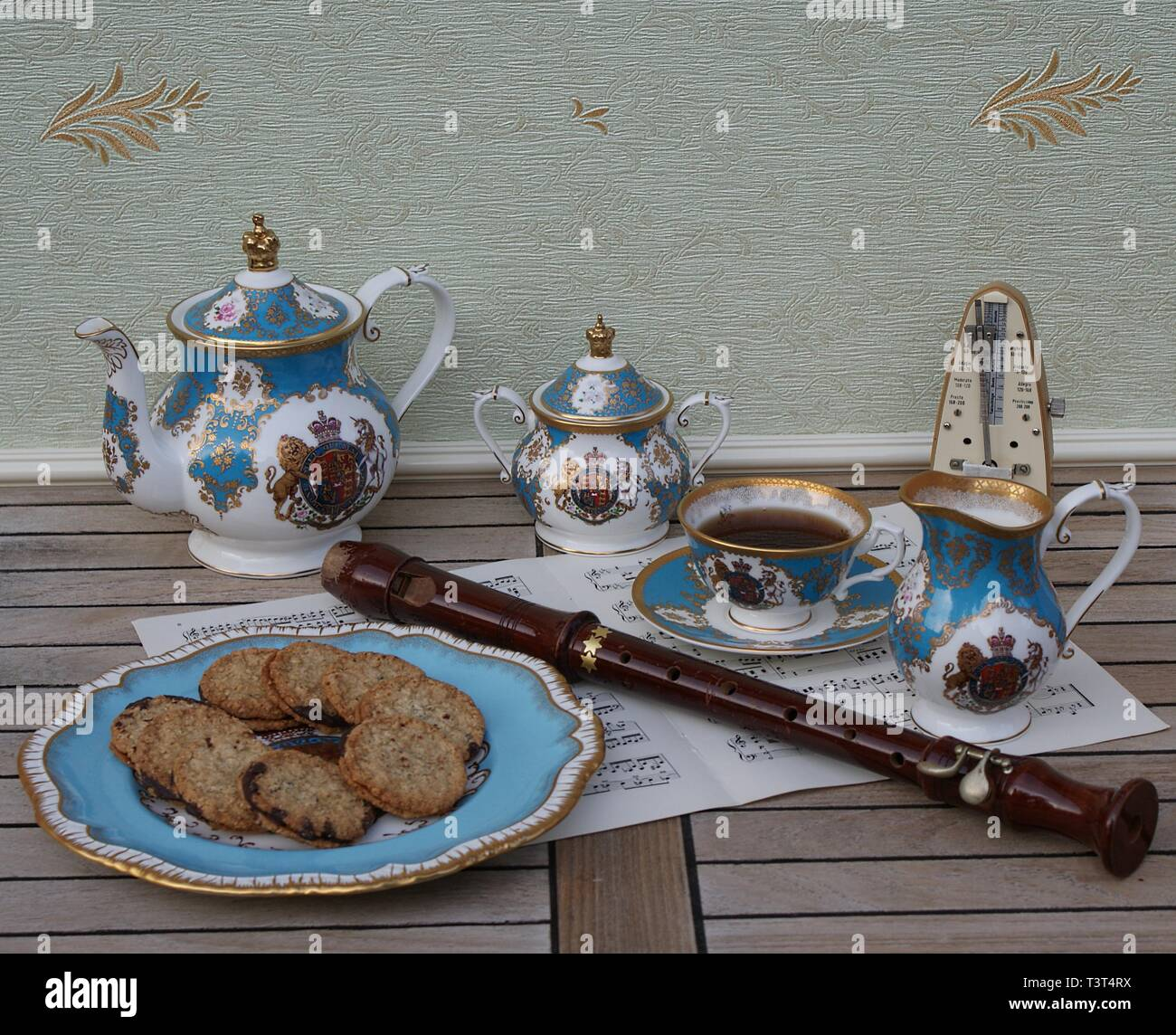 English teacup with saucer, teapot, sugar bowl, cream jug and a cake plate with cookies, metronome for music and a block flute on a sheet of music - Stock Image