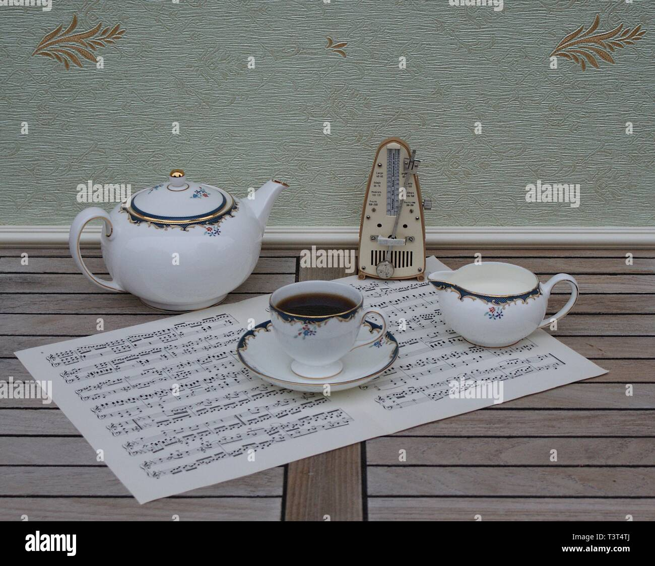 English teacup with saucer, teapot and cream jug, bone china porcelain, and a metronome for music on a sheet of music - Stock Image