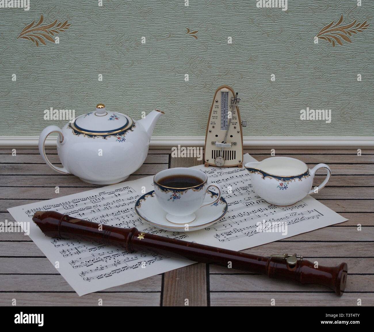 English teacup with saucer, teapot and cream jug, fine bone china porcelain, metronome for music and a block flute on a sheet of music - Stock Image