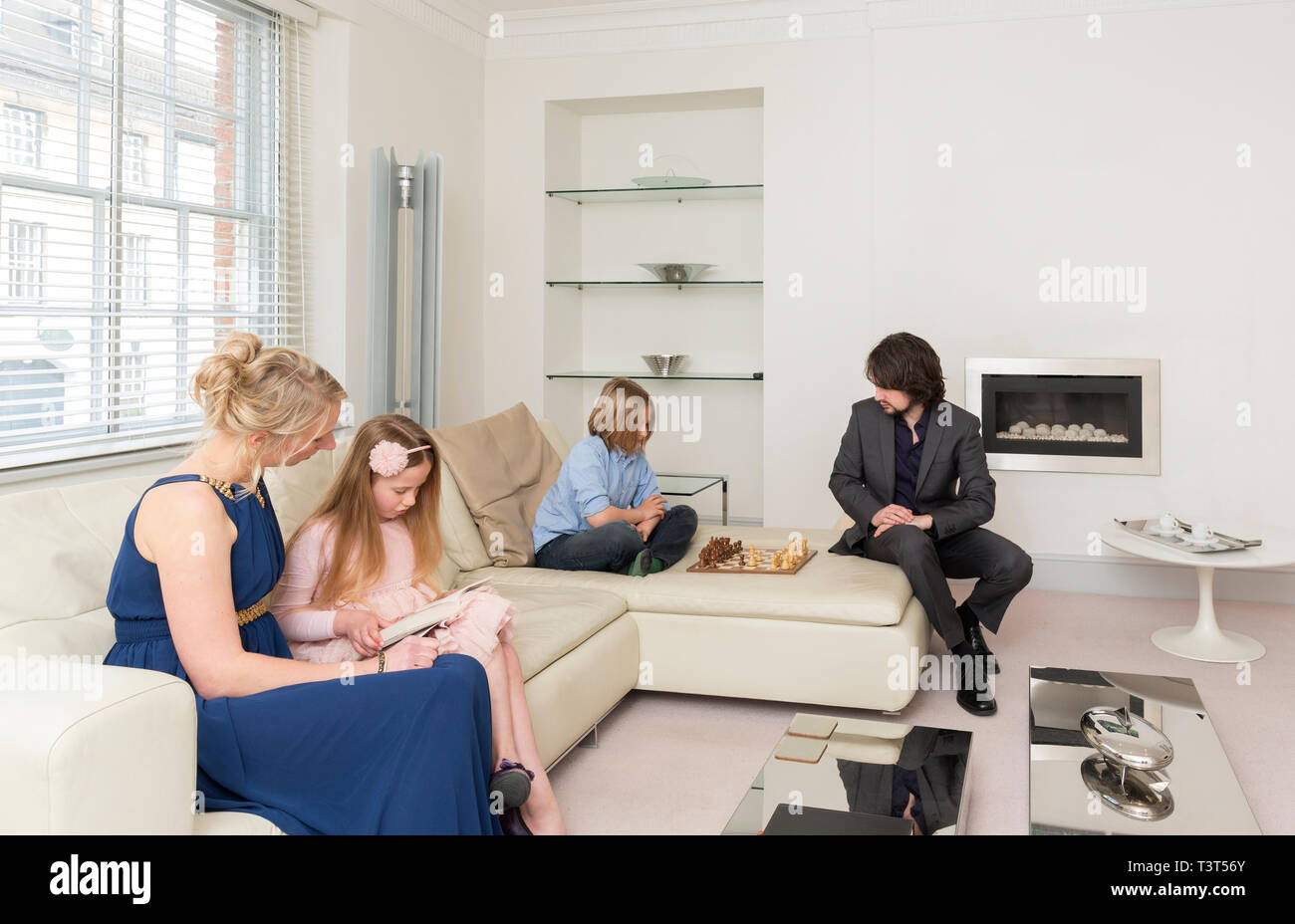 Caucasian family relaxing in living room - Stock Image