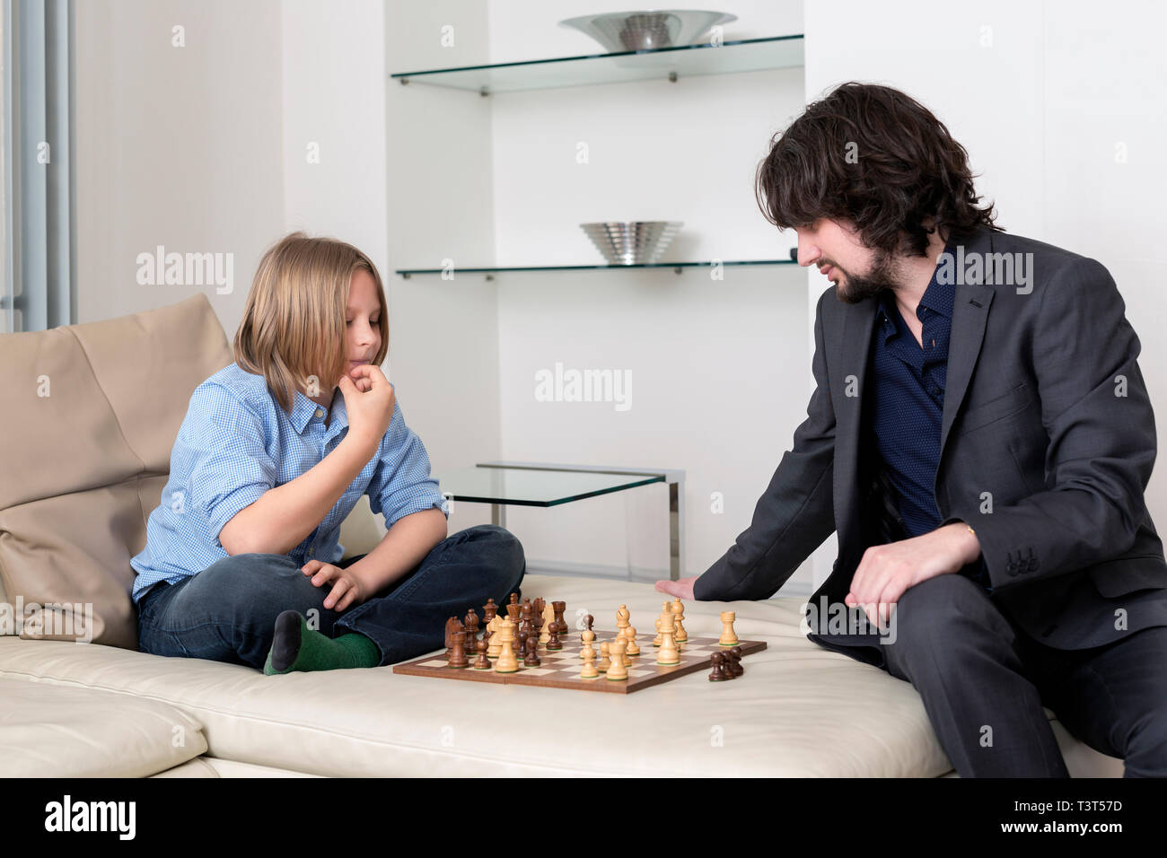 Caucasian father and son playing chess on sofa - Stock Image
