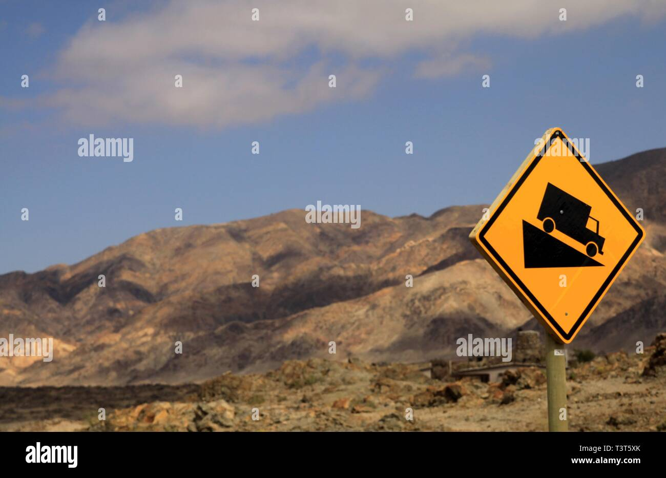 Yellow isolated sign with black truck in dry arid environment warning for steep gradient in Atacama desert, Chile - Stock Image