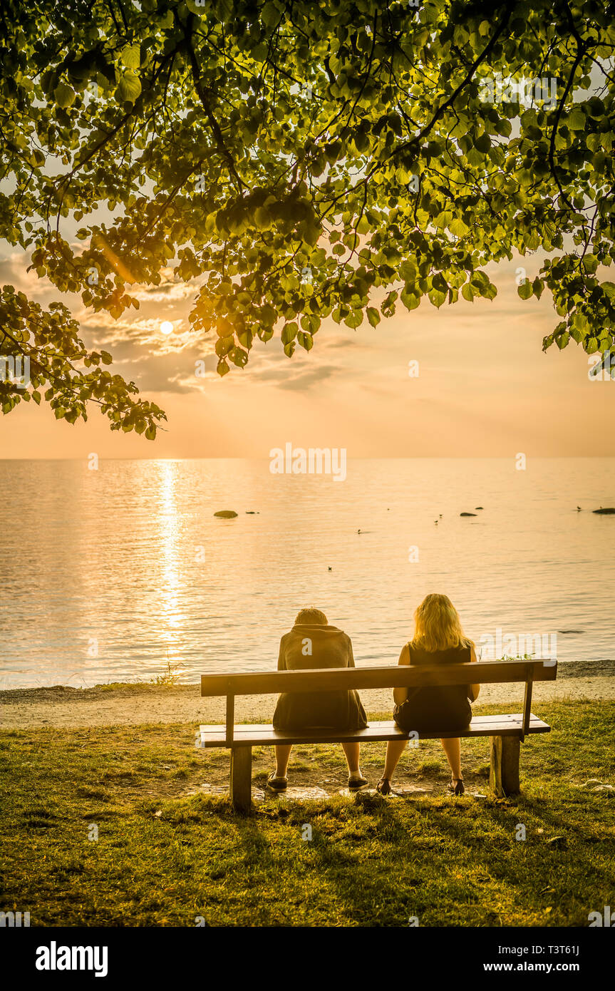 Couple on a bench by the sea at sunset. Visby, Gotland, Sweden, Scandinavia - Stock Image