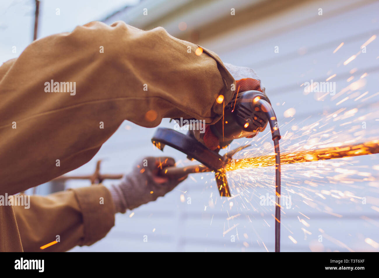 Sparks from the metal and grinder fly from under the grinding disc - Stock Image