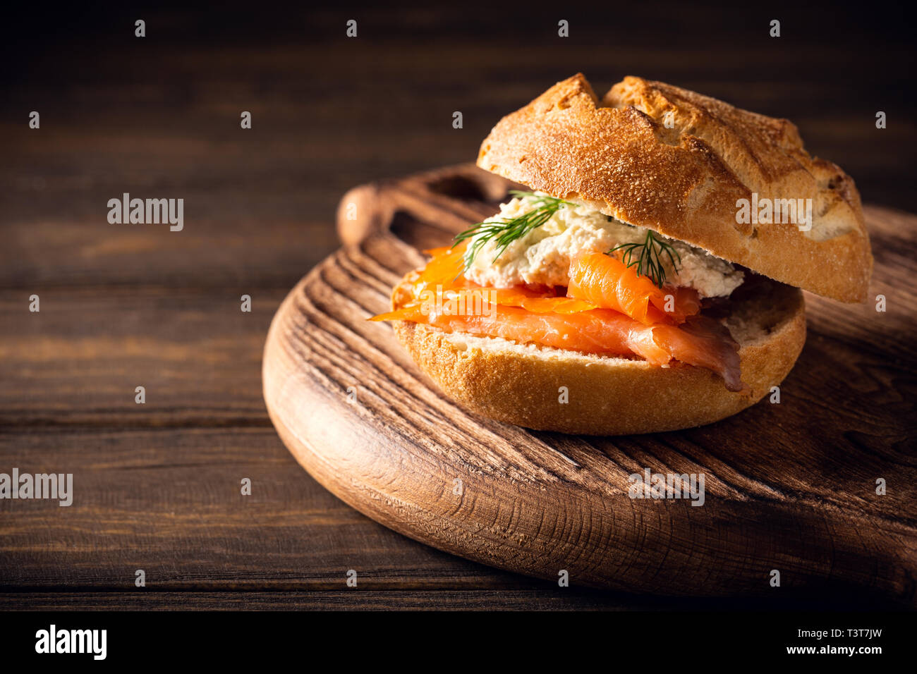 Sandwiche with salmon and herb butter on old wooden table. Healthy food background concept with copy space - Stock Image