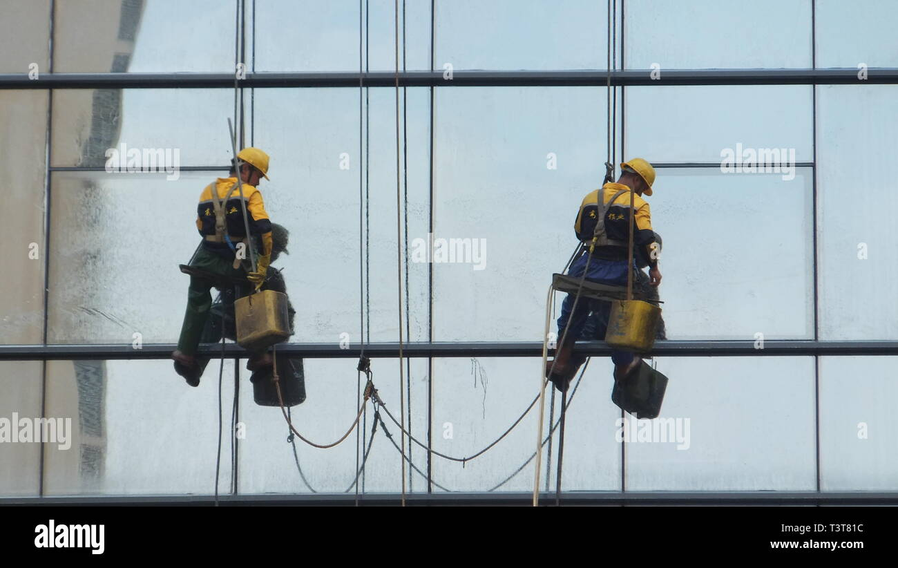 Workers clean the glass facade of a skyscraper in shenzhen, China Stock Photo