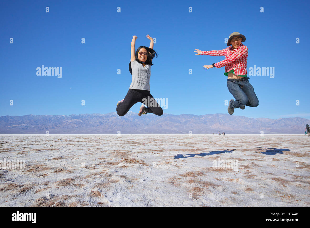 Asian couple jumping near mountain range - Stock Image