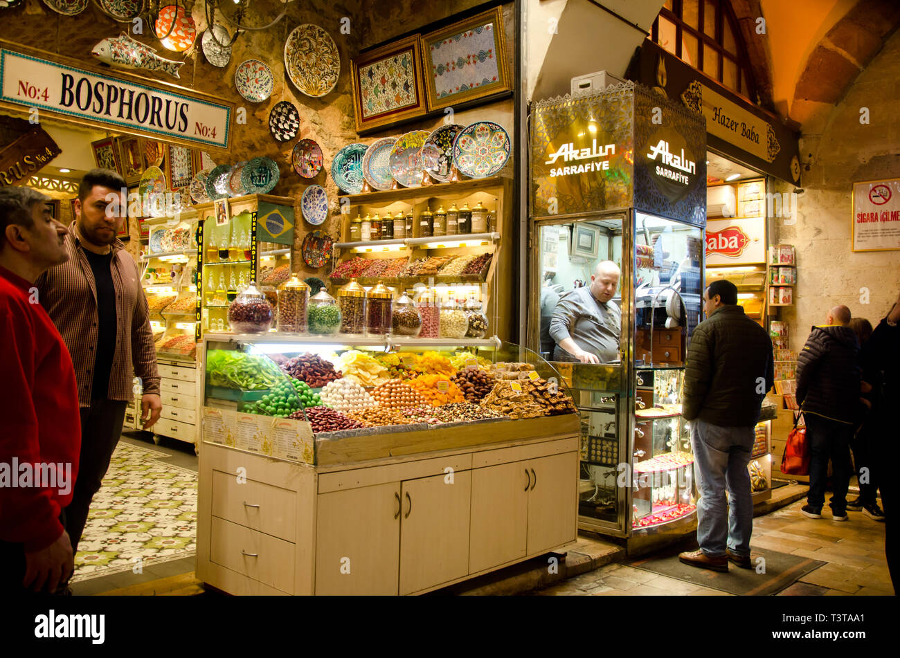 Istanbul, Turkey, March 07, 2019:market vendor standing in front of market store with various colorful sweets and souvenirs, inside of Egyptian Bazaar - Stock Image